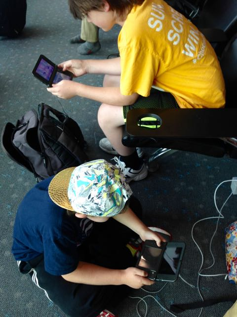 boys playing Nintendo 3DS at airport